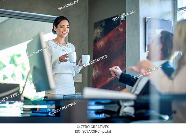 Office worker handing coffee to business team at office desk