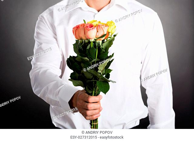 Close-up Of A Man Giving Bunch Of Roses As Present