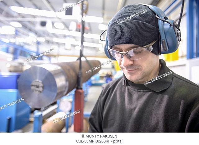 Worker wearing headphones in factory