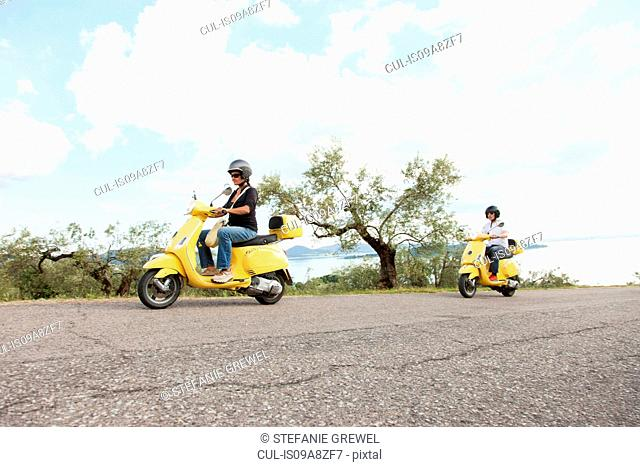 Couple on scooters riding up rural road