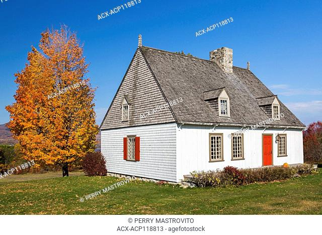 Old white with tan trim 1752 French regime cottage style home in autumn, Quebec, Canada. This image is property released for book, calendar, magazine
