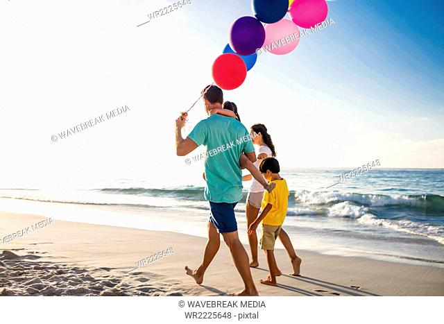 Cute family walking and holding balloons