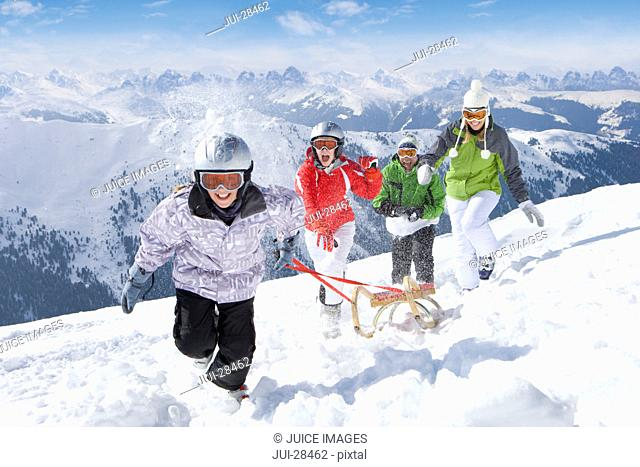 Smiling family pulling sled in snow on ski slope