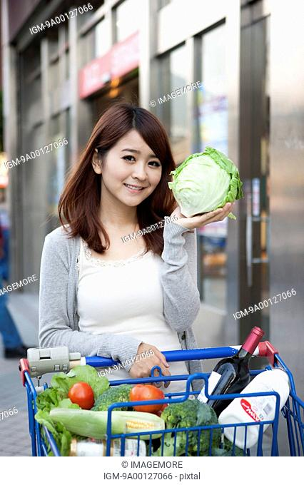 Young woman with shopping cart lifting a cabbage