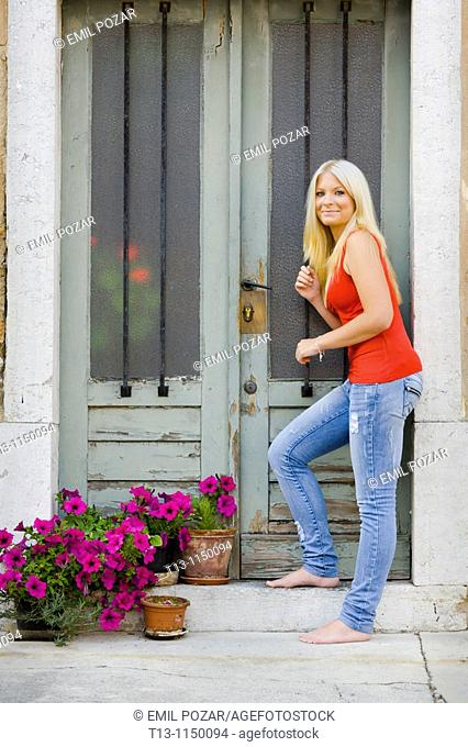Entering a traditional old-fashioned European house young woman