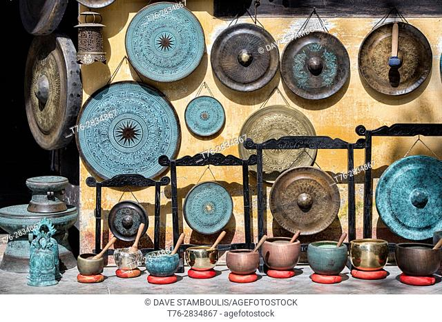 Traditional gongs for sale in an art shop, Hoi An, Vietnam