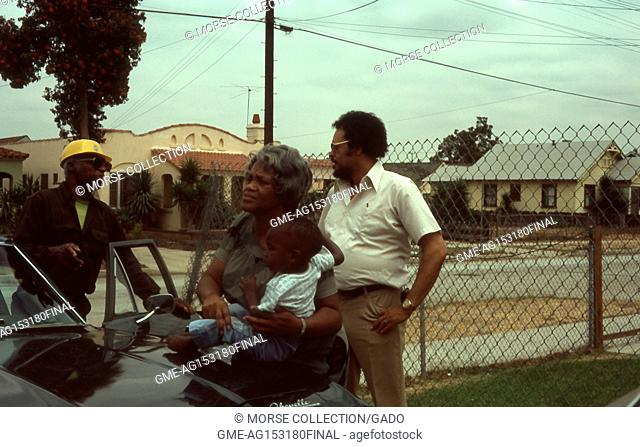 Scene of an African American family outside of their home in Los Angeles, California, 1977. An African American man wearing a yellow hardhat is visible as he...