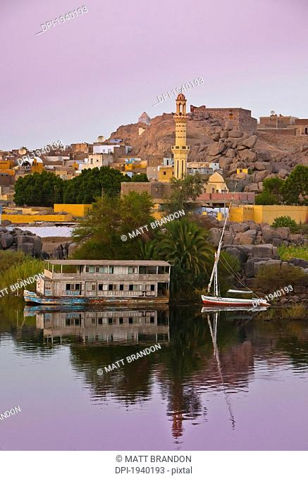 a sailboat on the river's edge with a view of the village at dusk, nubia egypt