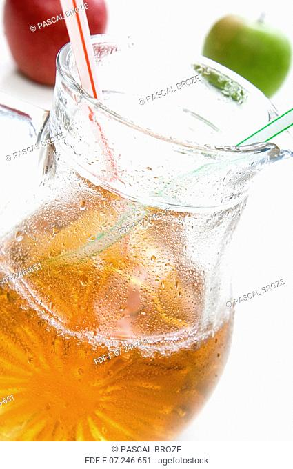 Close-up of a jug of apple juice with two drinking straws