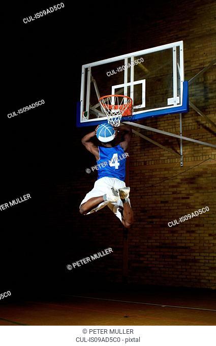 Basketball player jumping with ball