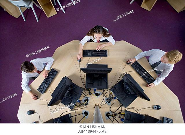 Overhead view schoolboys and schoolgirl in private school uniform using computers at table in computer lab classroom