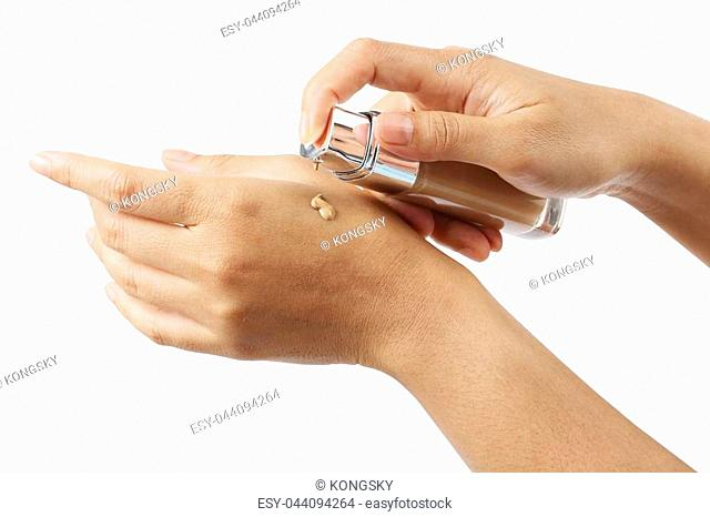 Woman puts a liquid foundation on her palm isolated on white background, clipping path