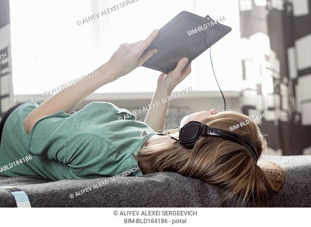 Caucasian woman using digital tablet on bed