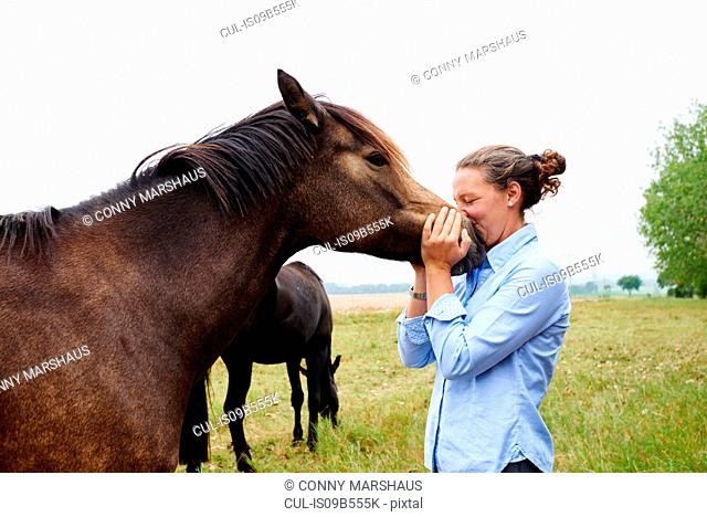 Woman with her face to horse's muzzle in field