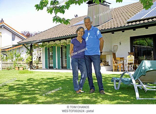 Germany, Bavaria, Senior couple standing in yard, smiling