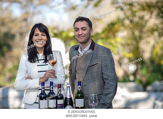 Smiling man and woman with assortment of wine