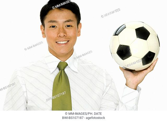 A young businessman holding a football
