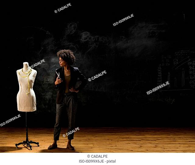 Businesswoman standing by blackboard with tailors dummy