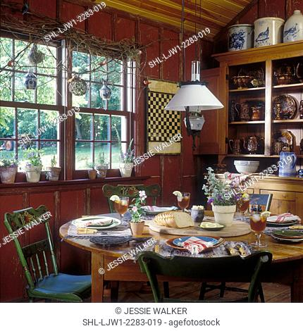 Kitchen Eating area, Bennington ware dishes. Rustic red walls, country styling,painted farm chairs , tole painted, game board