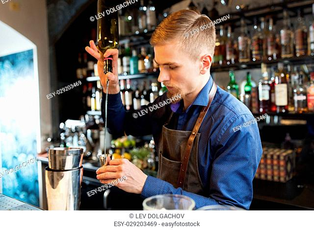drinks, people and luxury concept - barman with shaker pouring alcohol from bottle into jigger and preparing cocktail at bar