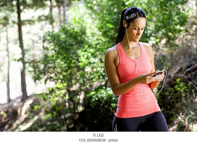 Female jogger using mp3 in forest