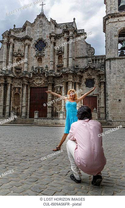 Young couple taking photographs in the colonial Plaza de la Cathedral of Havana, Cuba