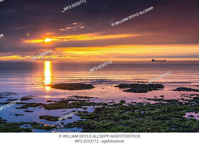The sun rises over a calm North Sea at Roker in Sunderland