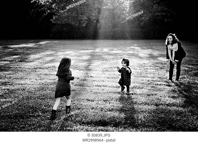 Woman and two girls standing outdoors on a lawn, playing