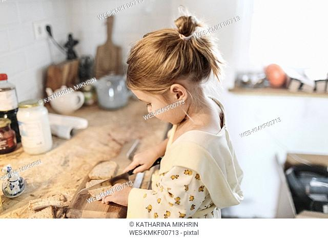 Little girl slicing bread in the kitchen