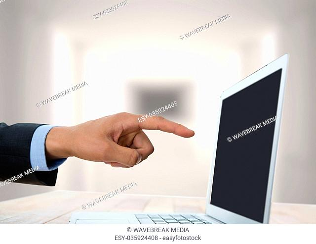 Hand pointing at laptop with bright background