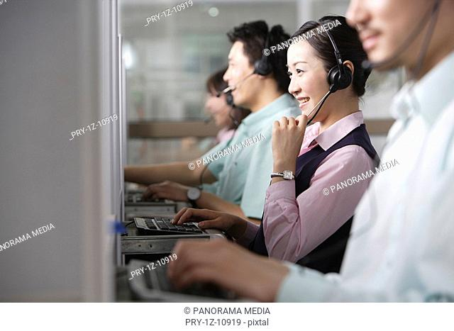 Young men and young women using PC with headset