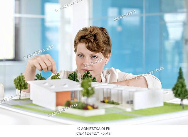 Female architect arranging building model in office