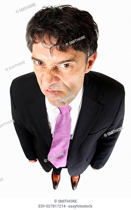 Fun high angle full length portrait oaf a nasty businessman with an attitude sneering at the camera and looking up under his eyebrows isolated on white