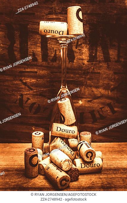 Wino still life art on a corks and a upside down wine glass on rustic vintage brown wooden bar background
