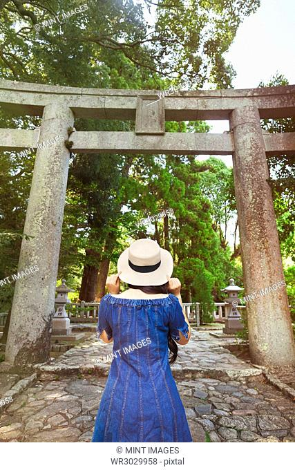 Rear view of young woman wearing blue dress and hat standing at Shinto Sakurai Shrine, Fukuoka, Japan