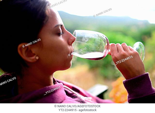Young woman smells and tastes cup of wine