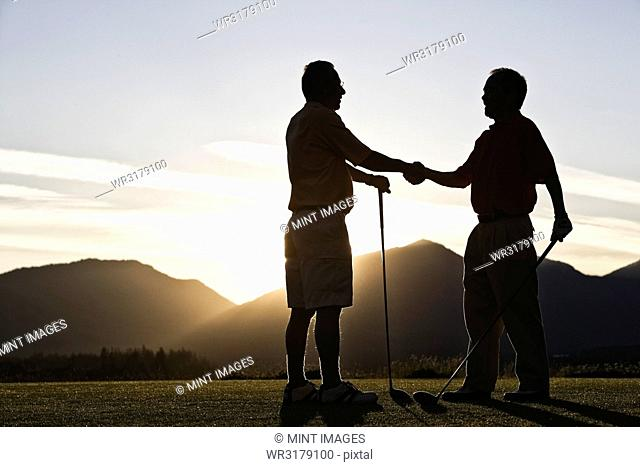 Two senior friends approach the first tee of a golf course at sunrise