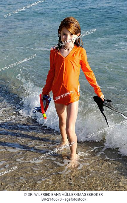 Girl with snorkeling gear, flippers and goggles on a beach by the sea