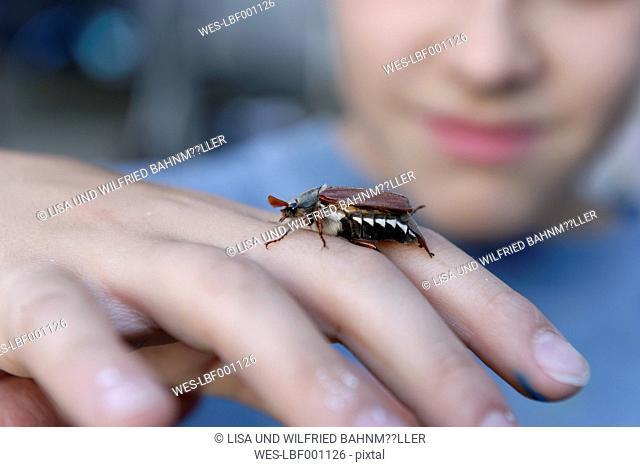Boy with maybug on his hand