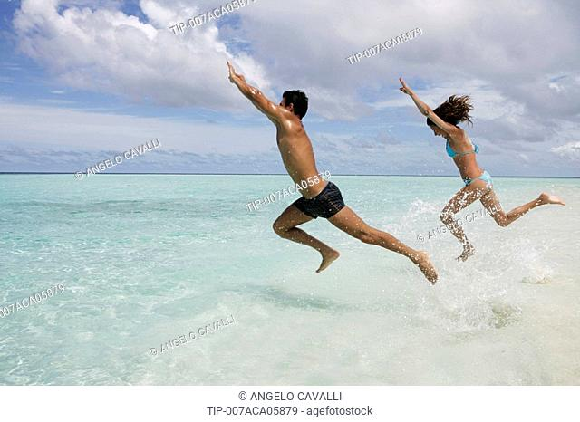 Couple at sea jumping in water