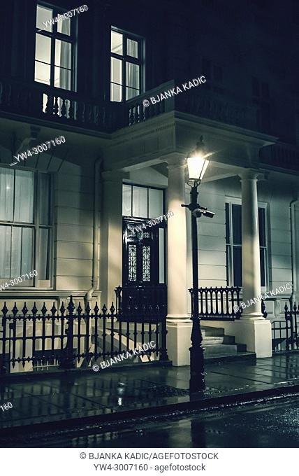 Lighted street lantern in front of a posh Georgian house at night, London, UK