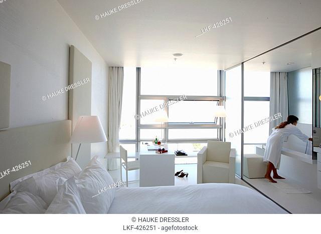 Woman wearing a bathrobe in a douple room at a hotel, Vienna, Austria
