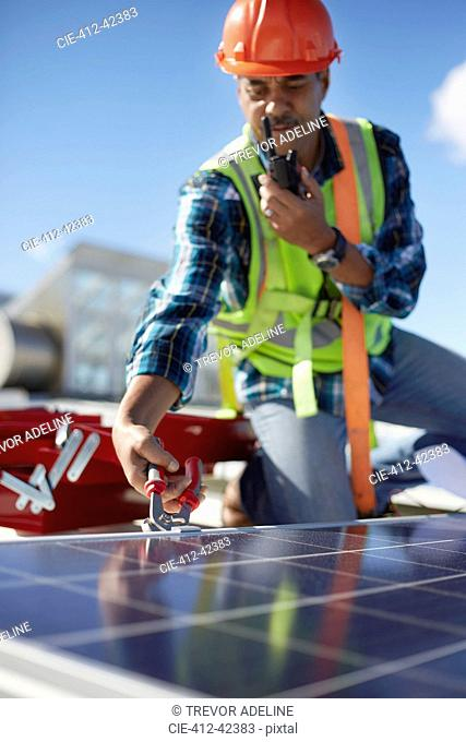 Male engineer with walkie-talkie repairing solar panel at power plant