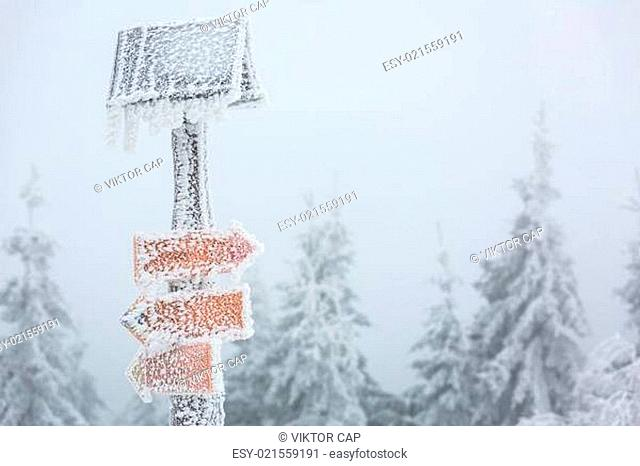 Extreme winter weather - hiking path sign covered with snow brought by strong wind during snowstorm
