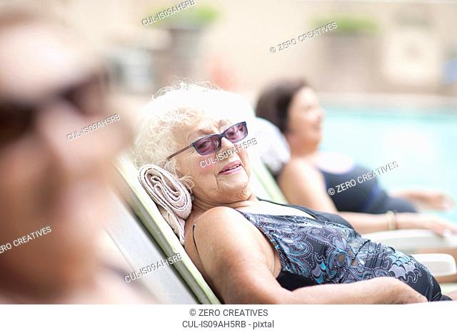 Senior women on sun loungers in retirement villa garden