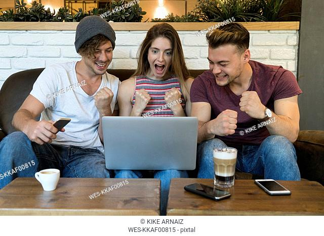 Three excited friends looking at laptop in a cafe