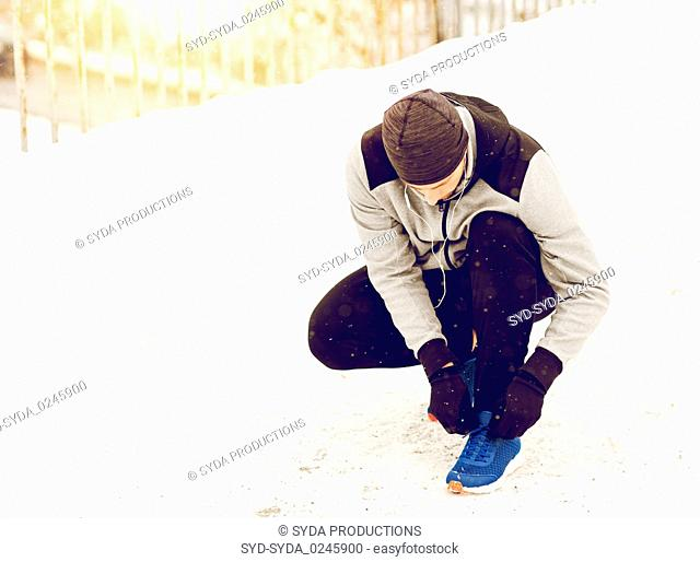 man with earphones tying sports shoe in winter