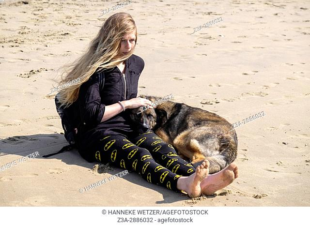 A girl and her dog at the beach of Scheveningen, The Hague, The Netherlands, Europe