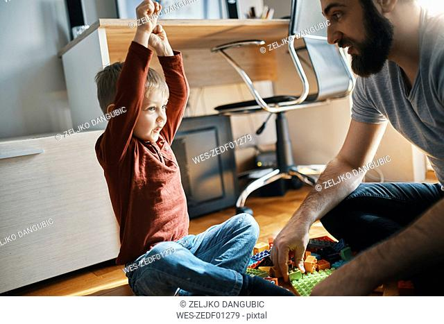 Father and son sitting on the floor at home playing together with building bricks