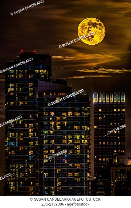 The super moon rises over the skyscrapers in the New York City skyline after sunset